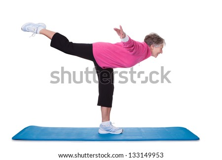 Senior Woman Standing On One Leg And Exercising Over White Background - stock photo