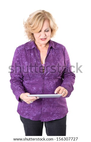 Senior woman standing with tablet computer over white background - stock photo
