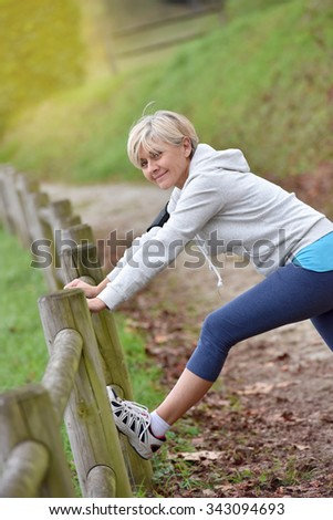 Senior woman stretching after exercising in natural landscape - stock photo