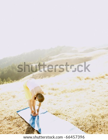 Senior woman stretching on a yoga mat outdoors - stock photo