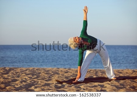Senior woman stretching on the sandy beach. Mature caucasian woman exercising by the sea. - stock photo