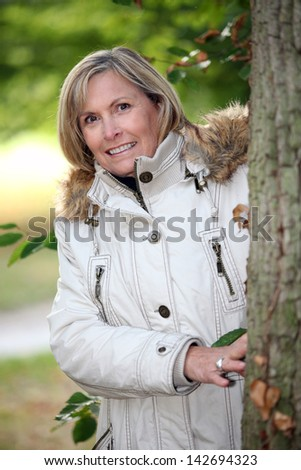 Senior woman strolling in the woods - stock photo