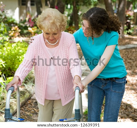 Senior woman struggles to walk with the help of a walker and her young granddaughter. - stock photo