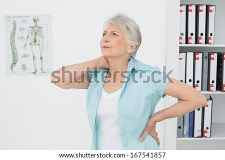 Senior woman suffering from neck pain standing in the medical office - stock photo