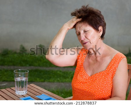 Senior woman suffers from headache, sitting at table with pills and glass of water - stock photo