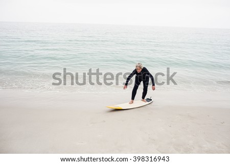 Senior woman surfing on surfboard at beach - stock photo