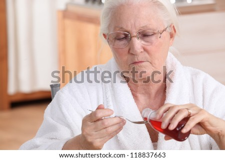 Senior woman taking cough syrup - stock photo
