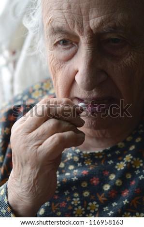 senior woman taking pill - stock photo