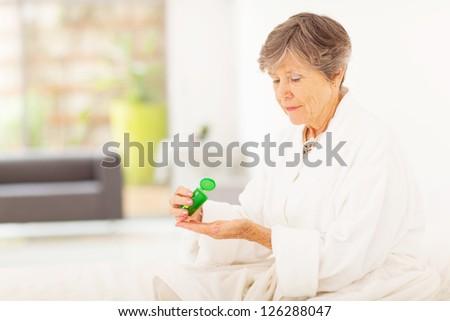 senior woman taking pills at home - stock photo