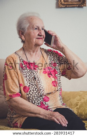Senior woman talking on a mobile phone and smiling - stock photo