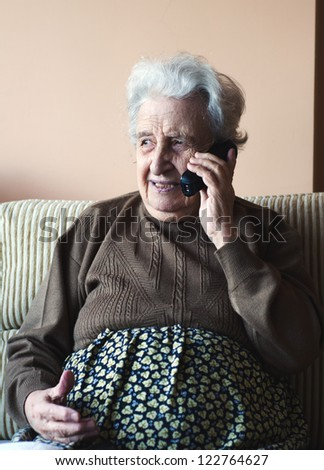 senior woman talking on phone indoor - stock photo