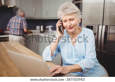 Senior woman talking on phone while using laptop and man working in kitchen at home - stock photo