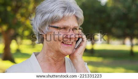 Senior woman talking on smartphone at the park - stock photo