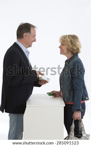 Senior woman talking with male pharmacist - stock photo