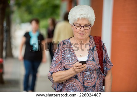 Senior woman text messaging on smartphone outdoors - stock photo