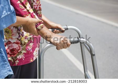 Senior woman using a walker cross road - stock photo