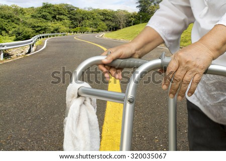 senior woman using a walker cross road. - stock photo