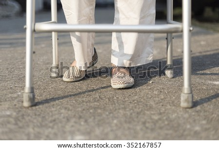senior woman using a walker cross street. - stock photo