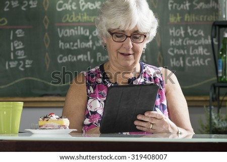 Senior woman using an ipad/tablet in a cafe - stock photo