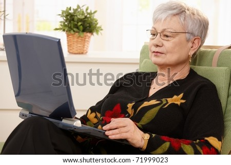 Senior woman using laptop computer at home, sitting in armchair.? - stock photo