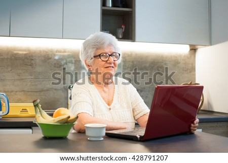 Senior woman using laptop computer while having coffee break in the kitchen. - stock photo