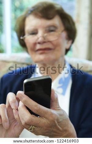 Senior Woman using Smart Phone at home - stock photo