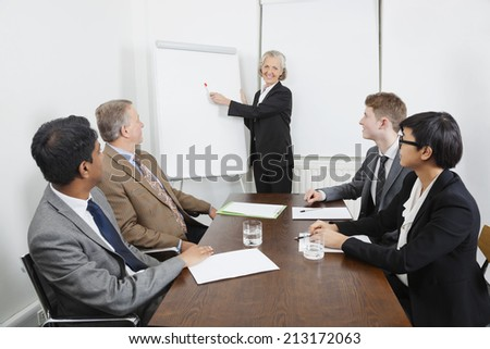Senior woman using whiteboard in business meeting - stock photo