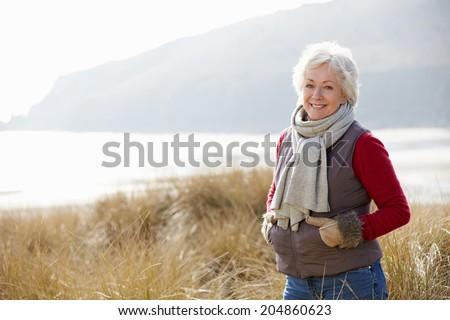 Senior Woman Walking Through Sand Dunes On Winter Beach - stock photo