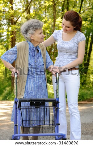 Senior  woman walking with the help of a granddaughter - stock photo