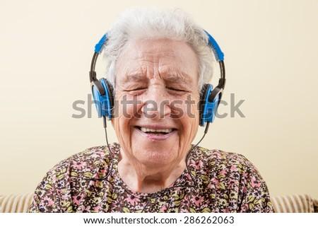 senior woman wearing headphones - stock photo