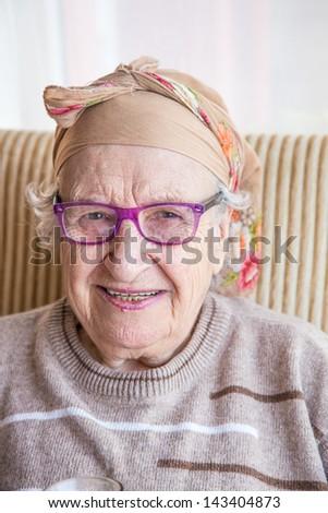 senior woman wearing headscarf and eyeglasses - stock photo