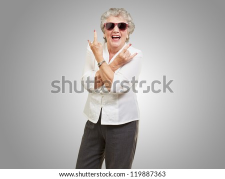 Senior woman wearing sunglasses doing funky action isolated on gray background - stock photo