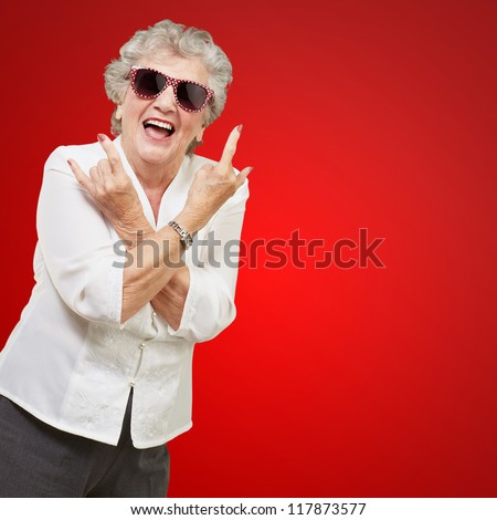 Senior woman wearing sunglasses doing funky action isolated on red background - stock photo