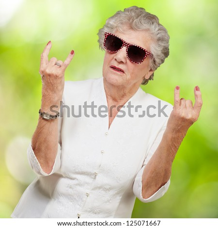 Senior woman wearing sunglasses doing funky action, outdoor - stock photo