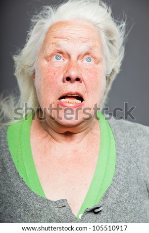 Senior woman white grey hair with expressive emotional face and hands. Studio shot isolated on grey background. - stock photo