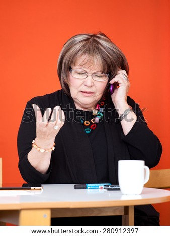 senior woman with arguing on phone - stock photo