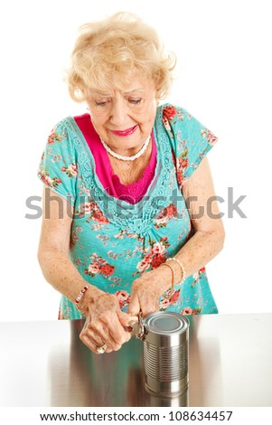Senior woman with arthritis struggles to open a can. - stock photo