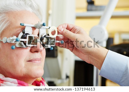 Senior woman with astigmatism and trial frame at the optician - stock photo
