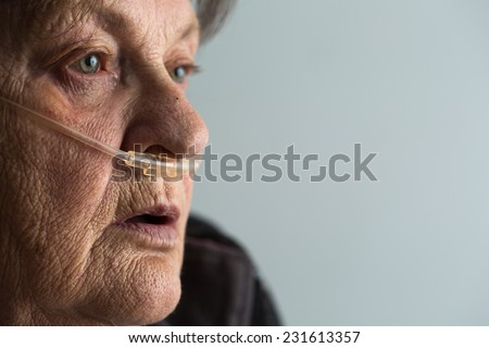 Senior woman with Chronic obstructive pulmonary disease with supplemental oxygen - stock photo