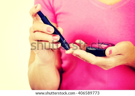 Senior woman with glucometer checking blood sugar level - stock photo
