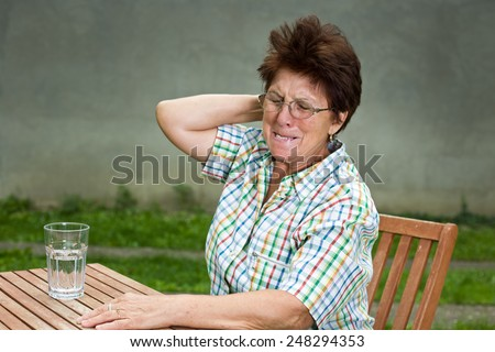 Senior woman with headache sitting in courtyard with glass of water on table - stock photo