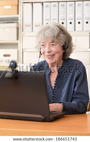 Senior woman with headphone smiling at the webcam of her laptop, copy space - stock photo
