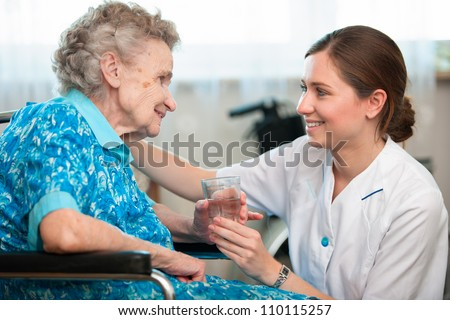 Senior woman with her caregiver at home - stock photo