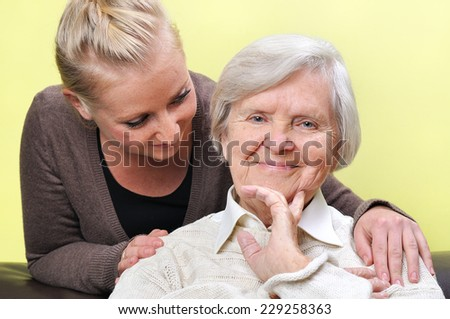 Senior woman with her caregiver.  Happy and smiling. - stock photo