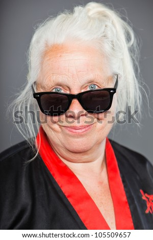 Senior woman with long grey hair wearing black and red kimono and black sunglasses. Cool looking. Studio shot isolated on grey background. - stock photo