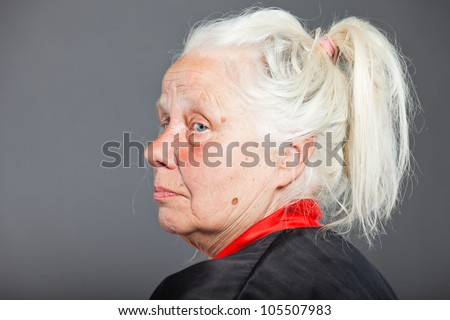 Senior woman with long grey hair wearing black and red kimono. Studio shot isolated on grey background. - stock photo