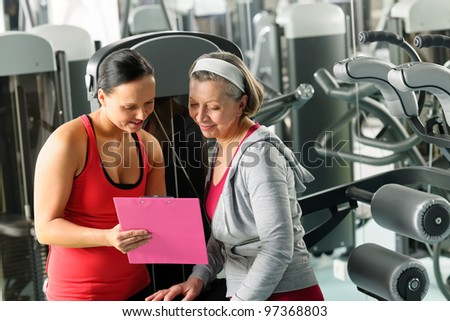 Senior woman with personal trainer looking exercise chart at gym - stock photo