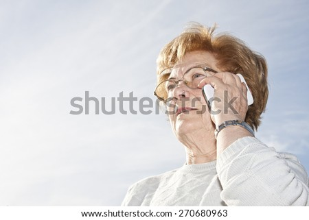 senior woman with phone outdoors - stock photo