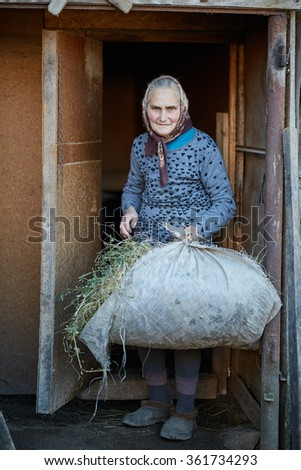 Senior woman with pile of hay at the stable entrance - stock photo