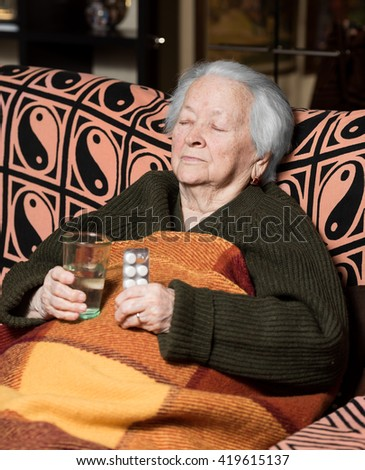 Senior woman with pills and glass of water at home - stock photo